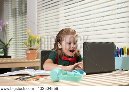 Child Boy Using A Laptop And Study Online Lesson. Pupil At School. Cute Child Using Laptop Computer,