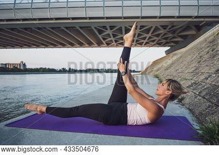 Woman Exercising Pilates Outdoor. Single Straight Leg Stretch Exercise.