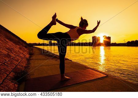 Young Woman Is Exercising Outdoor. She Is Practicing Yoga On Sunny Day. Natarajasana, Shiva Posture
