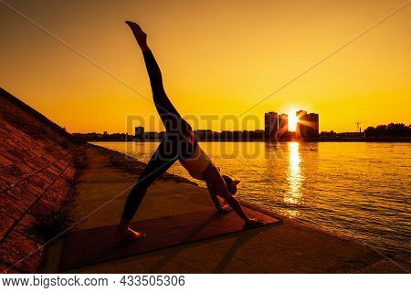 Young Woman Is Exercising Outdoor. She Is Practicing Yoga On Sunny Day. Eka Pada Adho Mukha Svanasan