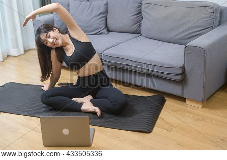 Young Woman Is Exercising And Watching Online Training Fitness Class On The Laptop In Living Room At