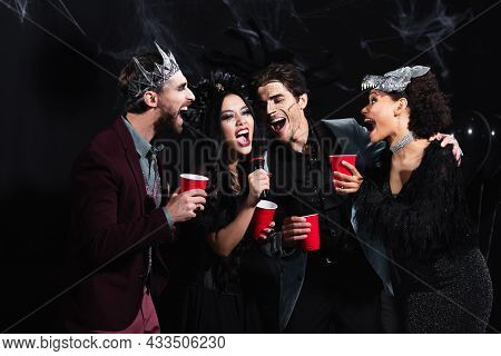 Excited Multiethnic Friends In Halloween Costumes Singing Karaoke On Black