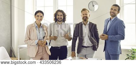 Portrait Of Four Confident, Friendly, Happy And Successful Business Partners In A Meeting In The Off