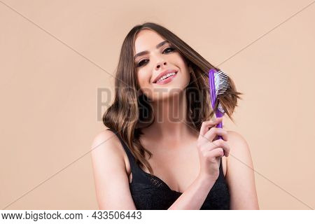 Young Beautiful Woman Combing Brown Hair. Hair Care. Beautiful Brunette Woman Hairbrushing Hair With