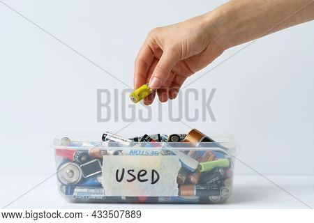Oslo, Norway - April 15, 2021.close Up Of Woman Arm Putting Used Discharged Battery In Plastic Conta