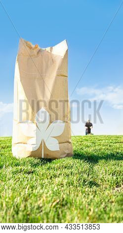 Brown Craft Paper Bag For Yard Waste Place On Green Grass Field Against Bright Blue Sky While Man Mo