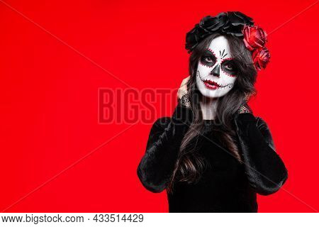 Girl With Creative Sugar Skull Makeup With A Wreath Of Flowers On Head, Wide Isolated On Red Backgro