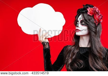 Girl With Creative Sugar Skull Makeup In Wreath Of Flowers On Head, Isolated On Red Background Hold