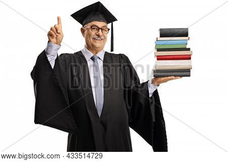 Smiling mature man in a graduation gown holding a pile of books and pointing up isolated on white background