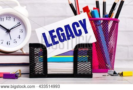 The Office Desk Has Diaries, An Alarm Clock, Stationery, And A White Card With The Text Legacy. Busi