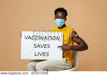 Young African American Guy Holding Placard With Vaccination Saves Life Motivational Inscription