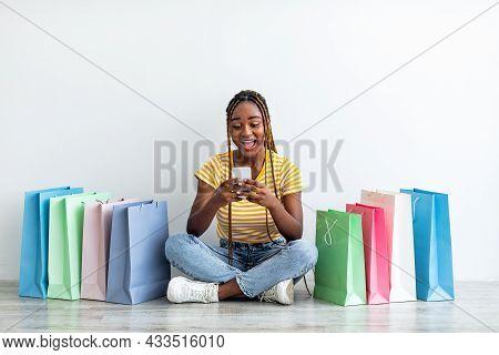 Positive Black Woman Shopaholic Purchasing Online, Using Smartphone