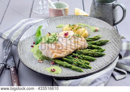 Modern style traditional fried skrei cod fish steak with green asparagus and potatoes served as close-up on a Nordic style plate