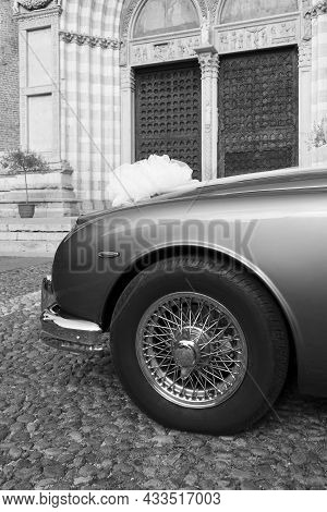 Part Of A Beautiful Wedding Car With A Front Wheel And A Bow On The Hood Against The Background Of A