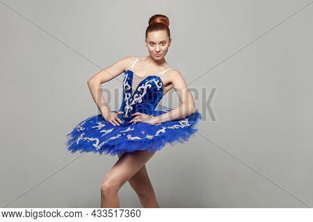 Portrait Of Beautiful Happy Ballerina Woman In Blue Costume With Makeup And Bun Collected Hair Stand