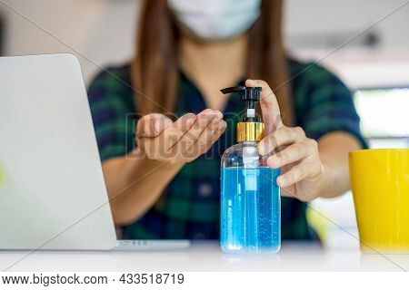 Closeup Asian Woman Hand Using Hand Sanitizer When Working At Home With Technology Laptop And Mobile