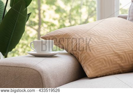 White Coffee Cup And Saucer Sits On The Arm Of The Living Room Sofa On The Background Of A Window Wi