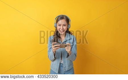 Asian Pretty Woman Gamer In Casual Clothing With Headset Playing Video Game With Mobile Smart Phone