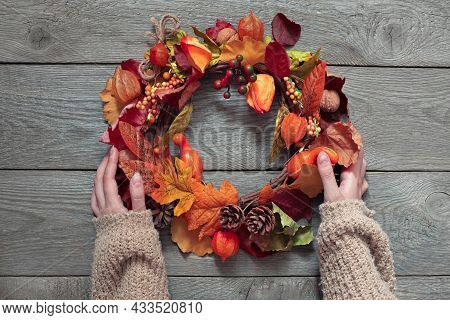 Hands Hold A Wreath Of Fruits And Leaves On A Wooden Background, Decorate A House For Thanksgiving,