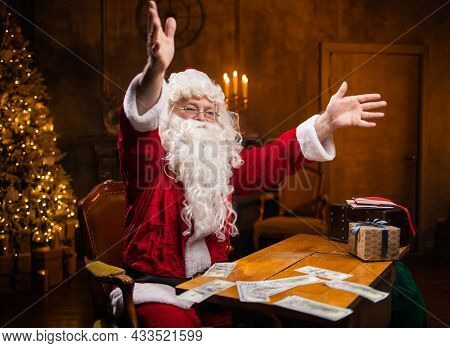 Workplace of Santa Claus. Cheerful Santa is counting money while sitting at the table. Fireplace and Christmas Tree in the background. Christmas concept.