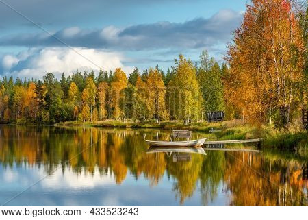 Beautiful fall scenery. Stunning morning view of calm water lake with a reflection of colorful autumn forest. Small wooden boat on the lakeshore at autumn in Finland. Ruska season in Finland.