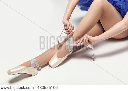 Ballerina Tying Pointe Shoes While Sitting Isolated On White Studio Background, Close-up. Indoor, St