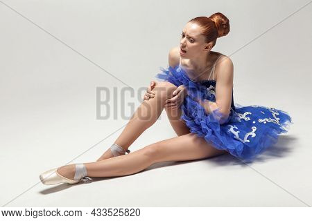 Knee Pain. Ballerina With Bun Collected Hair Wearing Blue Dress And Pointe Shoes Holding On Injured