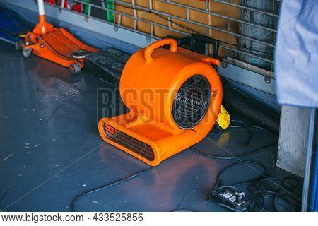 Orange Blower Fan Machine On Wet Floor. Heavy Duty Industrial Portable Blower Fan On Floor \nused To