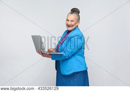 Aged Woman Standing And Holding Laptop And Looking At Camera With Smiley Face. Grandmother In Light