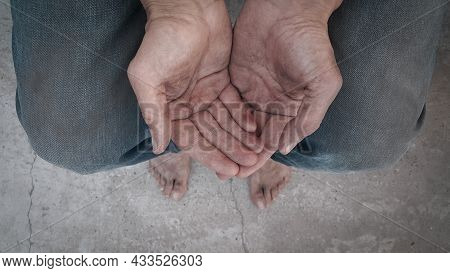 Begging. Outstretched Hands. Barefoot. A Homeless Person. Diminution Of Money. Poor Man. A Beggar In