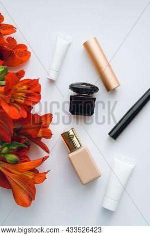 Flatlay Alstroemeria And Cosmetics On A White Background: Foundation, Perfume, Eyeliner, Eye Cream,
