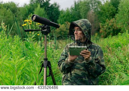 Man Ornitologist Looks At Or Writes Down Information On The Tablet While Standing Among The Tall Gra