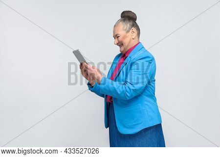 Profile View Of Aged Woman Holding Tablet And Looking At Screen With Satisfied Face And Toothy Smili