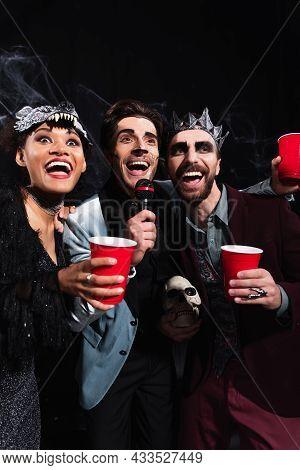 Happy Multiethnic Friends In Halloween Costumes Singing Karaoke On Black