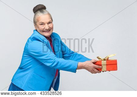 Happy Aged Woman Sharing Red Gift Box With Toothy Smiling. Portrait Of Happy Expressive Grandmother