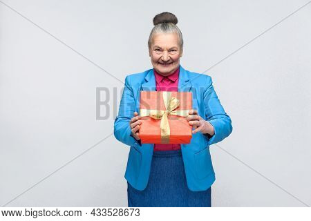 Happiness Woman Holding Red Gift Box And Toothy Smiling. Portrait Of Handsome Expressive Grandmother