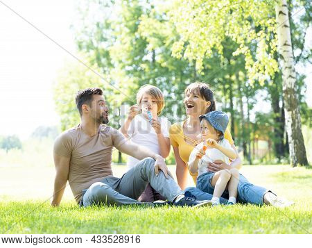 Happy Family Of Mother, Father And Two Children Blowing Bubbles In Summer Park