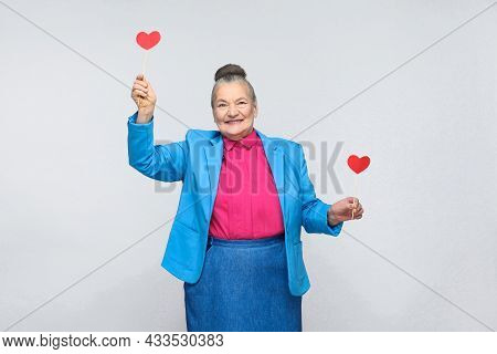 Happy Aged Woman Holding Two Red Heart Sign. Portrait Of Beautiful Happy And Satisfied Grandmother I