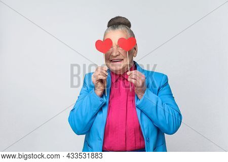 Happy Aged Woman Holding Two Red Small Heart Sign Before Eyes. Beautiful Funny Grandmother In Light