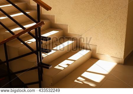 Sunlit Staircase With Railings In The House. Staircase At The Entrance Of An Apartment Building. Mod