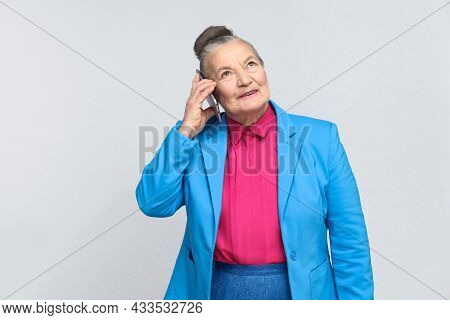 Aged Satisfied Woman Holding Mobile And Talking In Smart Phone And Smilling. Grandmother In Light Bl