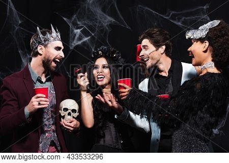 Happy Asian Woman In Vampire Halloween Costume Singing Karaoke Near Multiethnic Friends On Black