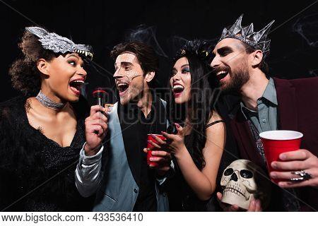 Joyful Multiethnic Friends In Spooky Costumes Singing Karaoke On Halloween Party On Black
