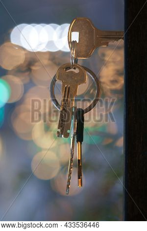 The Keys With House Keyring In The Door Keyhole With Blurred Night Lights Background, Selective Focu