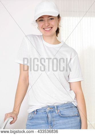 Female Model Wearing A White T-shirt And Baseball Cap. White Cap And T-shirt Mockup, Template For Pi