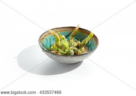 Fried tempura broccoli with peanut sauce in bowl. Vegeterian hot dish - florets cabbages roasted  in klar on white background. Veggie menu for asian restaurant. Hot vegan appetizers plant based