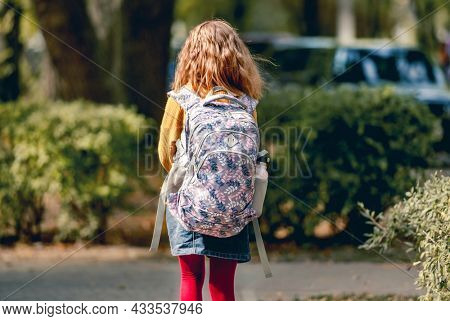 Preteen school girl with backpack outdoors from back. Pretty pupil female kid wit bag after education class in autumn park