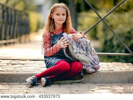 Preteen school girl with backpack sitting on ground and looking at camera. Sweet pupil female kid resting after education class in autumn park