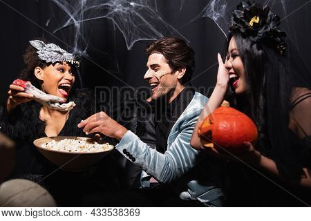 African American Woman Holding Spooky Toy Hand Near Interracial Friends Eating Popcorn On Halloween