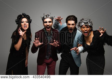 Multicultural Friends In Halloween Costumes Grimacing And Showing Scary Gesture At Camera Isolated O